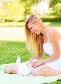 family, child and parenthood concept - happy mother with little baby lying on blanket in park