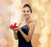 holidays, presents, luxury and happiness concept - smiling woman in dress holding red gift box over