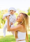 family, child, happiness and motherhood concept - happy mother with little baby sitting on blanket i