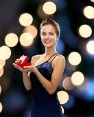 holidays, presents, luxury and happiness concept - smiling woman in dress holding red gift box night