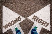 stock photo of morals  - Wrong and right dilemma concept with man legs from above standing on signs - JPG