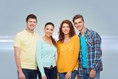 friendship, future and people concept - group of smiling teenagers standing over gray background wit