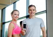 fitness, sport, advertising, technology and diet concept - smiling young woman and personal trainer