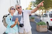 Happy tourist couple using tablet in the city on a sunny day