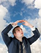 Businessman standing with hands over head against blue sky with white clouds