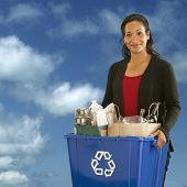 foto of recycling bins  - Pretty African American Woman holding a recyclables bin on a sky background - JPG