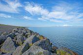 image of dike  - Dike of rocks and basalt along a lake in summer - JPG