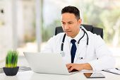 professional mid age medical doctor using laptop in office