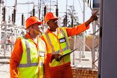 successful electrical engineers taking machine readings in substation