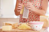Close Up Of Woman Grating Cheese In Kitchen