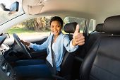 foto of seatbelt  - attractive young african female driver giving thumb up inside her new car - JPG
