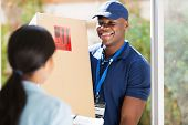 friendly young african american delivery man delivering a package
