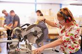 Female Student In Carpentry Class Using Circular Saw