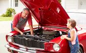 Grandfather And Granddaughter Working On Classic Car
