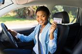 pretty african woman in a car showing her driver's license