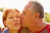 Affectionate Senior Couple Kissing In Garden