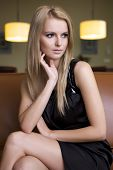 Portrait of attractive young adult blond woman in black dress sitting on the couch