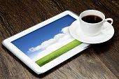 Tablet pc cup of coffee on wooden table