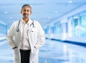 Indian doctor. Mature Indian male medical doctor standing inside hospital. Handsome Indian model por