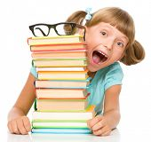 Cute little girl with books wearing glasses, isolated over white