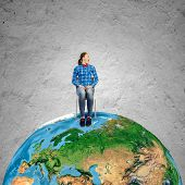 Young girl in shirt sitting on chair on Earth planet. Elements of this image are furnished by NASA