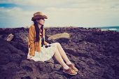 girl sitting on the rocks on the ocean shore