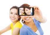 Two Happy Young Girls Taking A Selfie Over White Background