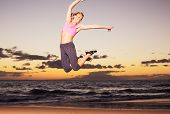 Attractive young happy fitness woman jumping on the beach at sunset