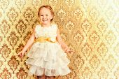 Happy little girl in a beautiful white dress standing by the vintage wall. Childhood. Holiday, birth