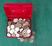 Rectangular red open suitcase with Ukrainian coins on wooden table