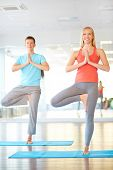 Portrait of young woman and man doing yoga exercise in gym