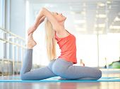 Happy female doing stretching exercise in gym