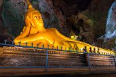PHANG NGA, THAILAND - 8 NOV 2012: Lying gold Buddha in the temple of Wat Tham Suwan Khuha cave. This natural temple with several large Buddha statues is a tourist attraction in Phang Nga, Thailand.
