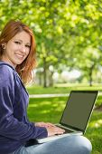 Pretty redhead relaxing in the park using laptop on a sunny day
