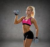 fitness, sport, exercising and people concept - sporty woman with heavy steel dumbbells over concret