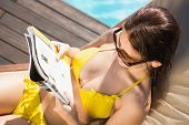 High angle view of a young woman reading book on sun lounger by swimming pool