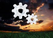 Cloud cog and wheel against green grass under dark blue and orange sky