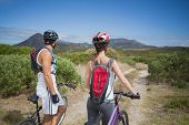 Rear view of an athletic couple mountain biking
