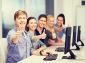 education, techology and internet concept - group of smiling students with computer monitor showing thumbs up at school