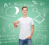 gesture, advertising, education, school and people concept - smiling young man in blank white t-shirt pointing fingers on himself over green board background with doodles