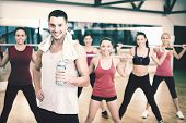fitness, sport, training, gym and lifestyle concept - smiling trainer in front of group of people wo