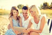 summer holidays, family, child and technology concept - smiling family at beach with tablet pc compu