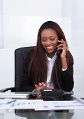 Happy Businesswoman Making A Call From Landline