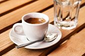 White Espresso Cup And Glass Of Cold Water Standing On The Wooden Table