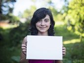 Young girl holding clean white sheet paper, outdoors (for your message)