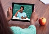 stock photo of students classroom  - Cropped image of female teacher assisting student through video conferencing at classroom - JPG