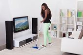 Woman Cleaning Floor In Living Room