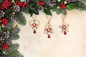Old fashioned christmas tree decorations with winter floral border of fir, holly, mistletoe and pine