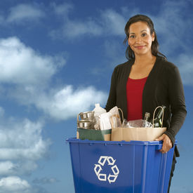 stock photo of recycle bin  - Pretty African American Woman holding a recyclables bin on a sky background - JPG