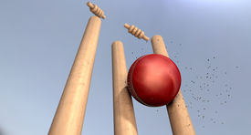image of cricket shots  - A red leather cricket ball hitting wooden cricket wickets on a blue sky background - JPG